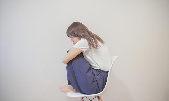 悲しい、悔しい表情をした女性が椅子に座っている画像